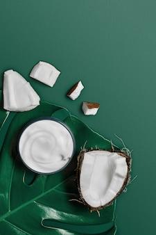 エキゾチックなトロピカルリーフの瓶入りホワイトクリームとトレンディなダークグリーンエデンのココナッツ。美しさと健康管理の概念。ミニマルなフラットレイアウトコピースペース。上面図