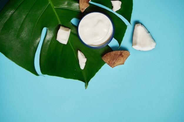 瓶に白いクリームとココナッツ、青と熱帯の葉にアーモンド。美しさと健康管理の概念。ミニマルなフラットレイアウトコピースペース。上面図。化粧品ナチュラルスキンケア