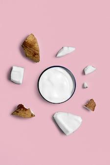 トレンディなピンクにココナッツを入れた瓶入りのホワイトクリーム。美しさと健康管理の概念。ミニマルなフラットレイアウトコピースペース。上面図。化粧品ナチュラルスキンケア