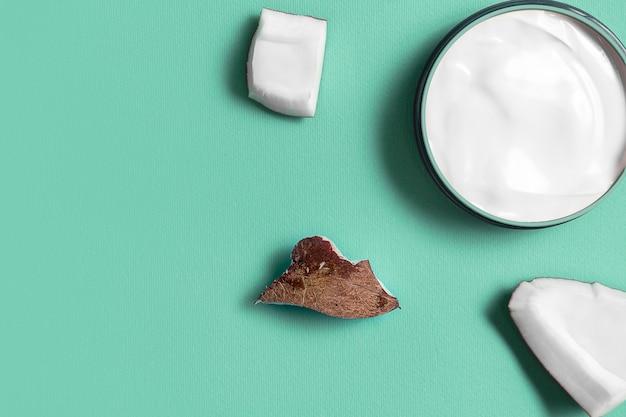トレンディなターコイズにココナッツを入れた瓶入りのホワイトクリーム。美しさと健康管理の概念。ミニマルなフラットレイアウトコピースペース。上面図。化粧品ナチュラルスキンケア