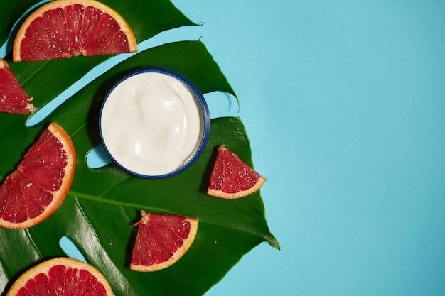青とトロピカルリーフにグレープフルーツの瓶に白いクリーム。美しさと健康管理の概念。ミニマルなフラットレイアウトコピースペース。上面図。化粧品ナチュラルスキンケア