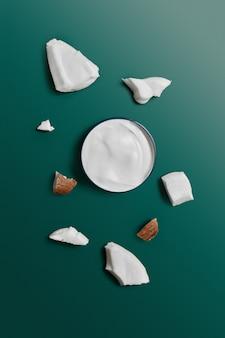 トレンディな濃い緑色のエデンにココナッツが入った瓶に入った白いクリーム。美しさと健康管理の概念。ミニマルなフラットレイアウトコピースペース。上面図