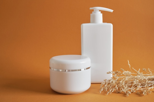 White cream jar and white bottle with dispenser without label on brown background, dry herb, natural cosmetics concept