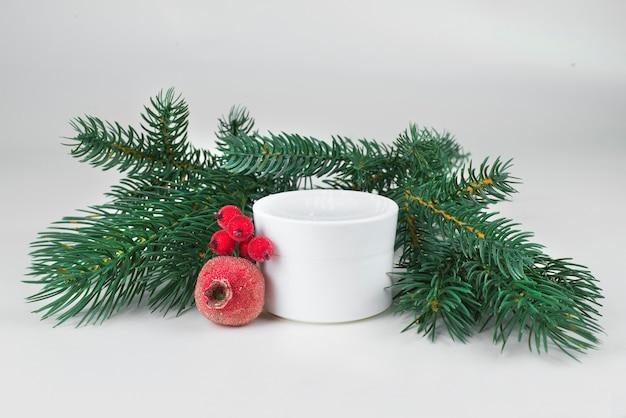 Белая кремовая банка с ветками елки и красными новогодними вещами на светлом фоне