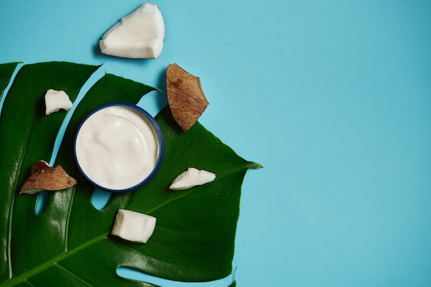 White cream in a jar on with coconut, almonds on blue and tropical leaf. beauty and health care concept. minimalistic flat lay with copy space. top view. cosmetic natural skin care