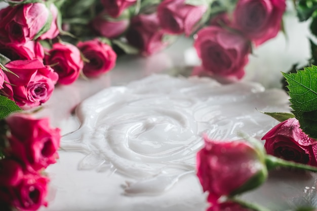 흐릿한 섬세한 핑크 장미로 둘러싸인 광택 표면에 흰색 크림