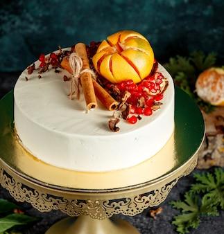 White creamy cake decorated with orange cinnamon sticks and pomegranates