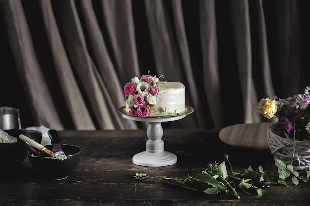 White creamy cake decorated with roses in dark interior