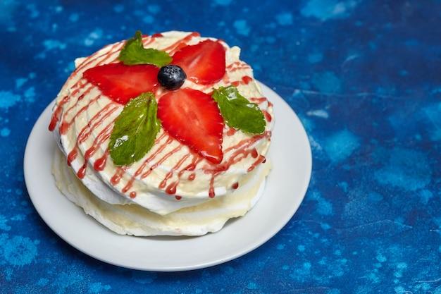 イチゴとミントの皿の上の白いクリーミーな丸いケーキ