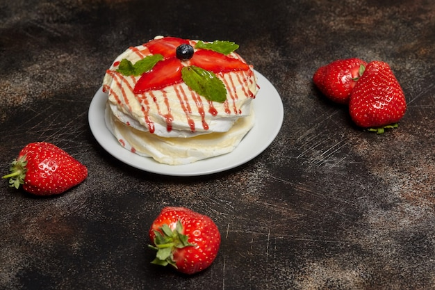 White creamy round cake with strawberries and mint on plate