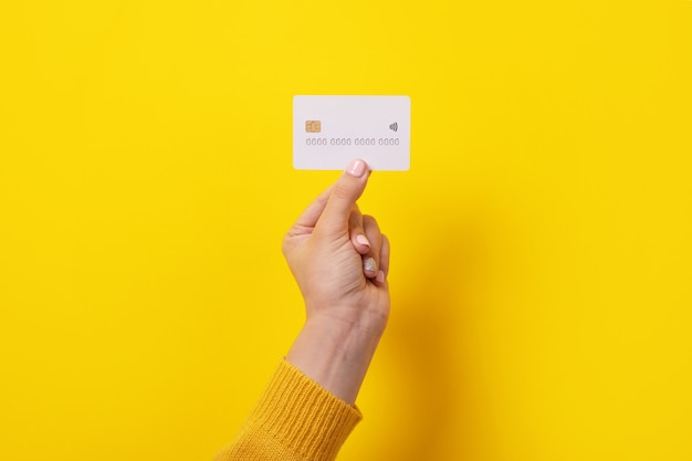 Белая кредитная карта в женской руке, карта с электронным чипом на желтом фоне