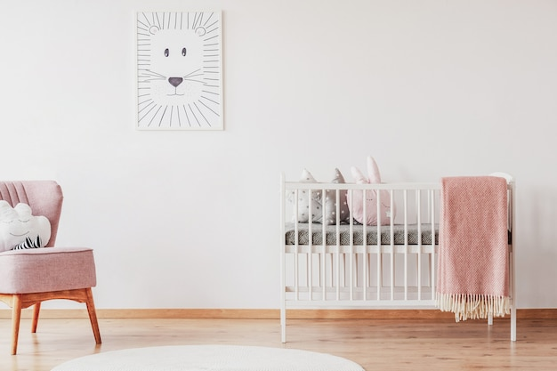 White crib with pillows and pink blanket in cute baby room with posters on the wall and pink armchair with cloud shape pillow