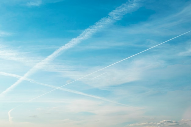 White crisscrossing trails of airplanes, traces of planes on blue sky as background