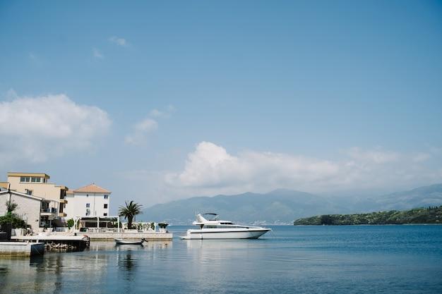 山々を背景にしたコテージのそばの桟橋にある白いクルーズヨット