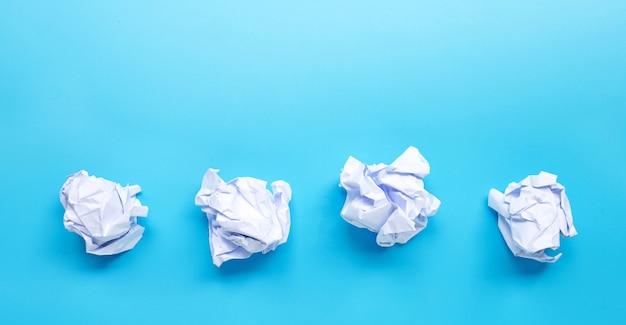 青の背景に白のしわくちゃの紙のボール。コピースペース