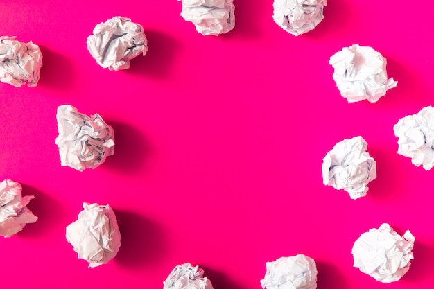 White crumpled paper ball on pink background