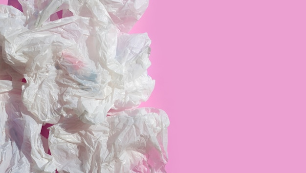White crumpled plastic bags on pink surface