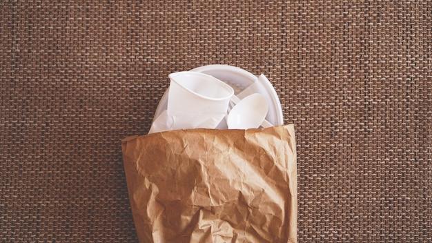 ベージュの背景に紙のパケットの白いしわくちゃのプラスチック皿。プラスチックとエコロジーのリサイクルの概念