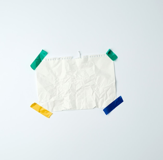 Белый мятый лист бумаги, вырванный из спиральной тетради и приклеенный изолентой на белом