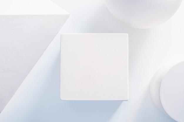 石膏の幾何学的形状の真ん中にある白い立方体の表彰台