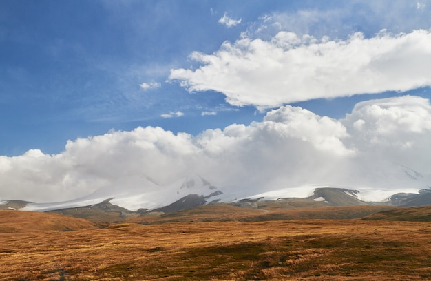 White cumulus clouds come down from the mountains, autumn landscape in the steppe