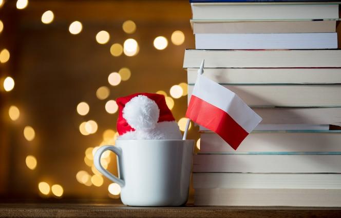本の近くの白い旗と白いカップとクリスマス帽子