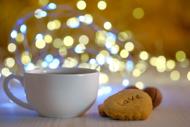 Белая чашка и печенье на фоне золотого бокэ