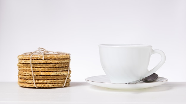 밝은 배경의 테이블에 흰색 컵과 접시, 수제 와플이 있습니다. 차와 함께 만든 수제 케이크.