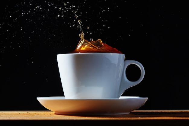 Белая чашка и блюдце с вкраплениями кофе.