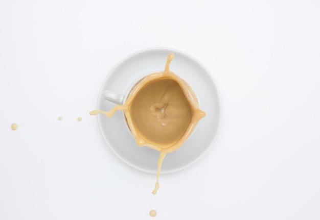 Белая чашка и блюдце с капучино и всплеск
