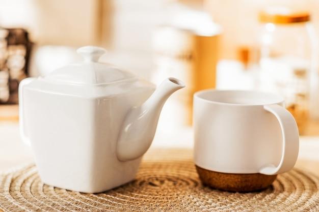 白いカップとティーポットが籐のナプキンのテーブルの上に立っています。横の写真