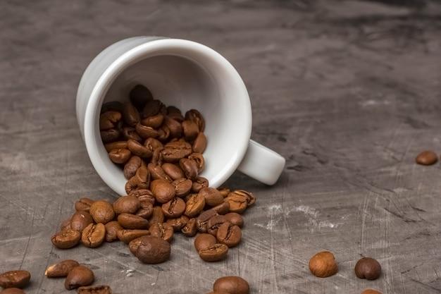 Белая чашка и цельные зерна кофе темный фон