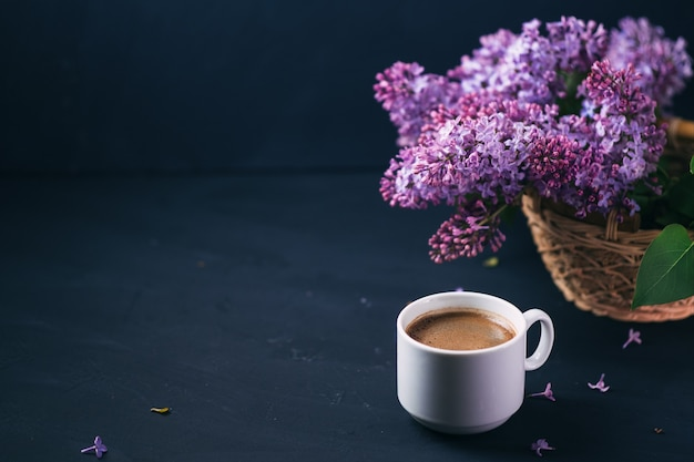White cup of aromatic espresso coffee on a dark stone table, blooming branches of purple lilac, copy space
