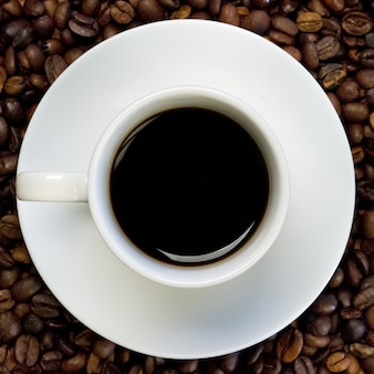 A white cup of black coffee on a surface full of coffee beans