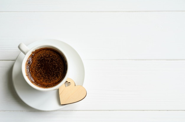 White cup of black coffee with a small wooden heart on the side