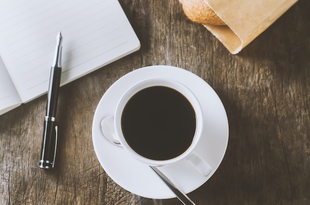 White cup of black coffee with white notebook and pen on wooden table