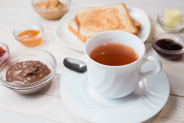 A white cup of black tea with sandwiches or toasts with peanut butter, chocolate paste and strawberry, currant and apricot jelly or jam on white wooden table, close up, breakfast concept