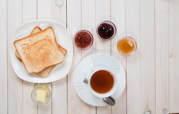 A white cup of black tea with sandwiches or toasts with strawberry, currant and apricot jelly or jam on white wooden table, top view, flat lay, breakfast concept with copy space