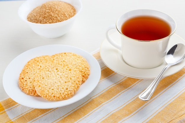 White cup of black tea with sesame cookies on the table