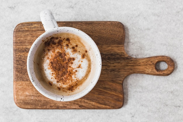 White cup of cappuccino sprinkled with powdered chocolate on chopping board