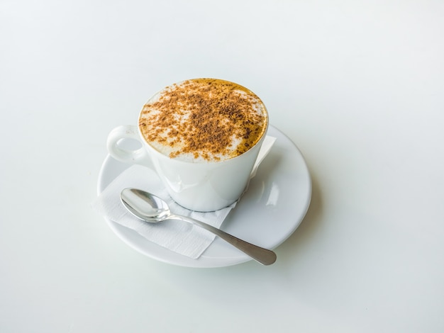 White cup of cappuccino on a white table.