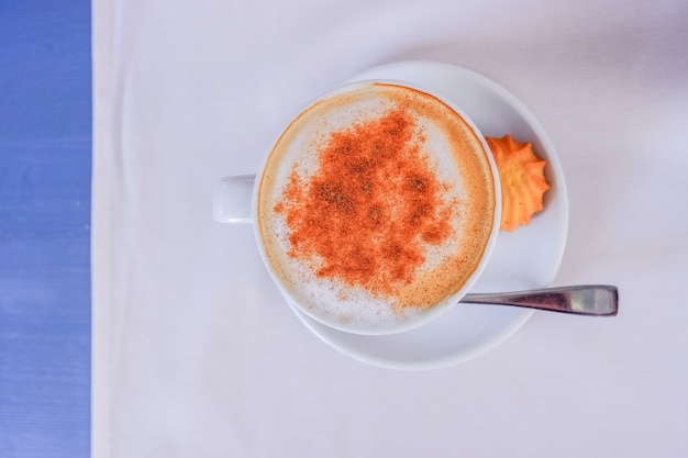 White cup of cappuccino with cinnamon on the light blue table with white napkin, top view. good morning coffee. hot drinks concept. copy space
