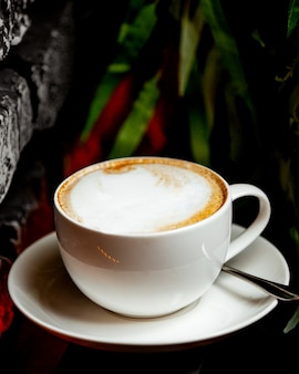 A white cup of cappuccino with foam on top