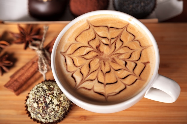 White cup of cappuccino with a latte-art pattern in the form of a flower. coffee, cake, cinnamon, anise, wooden table