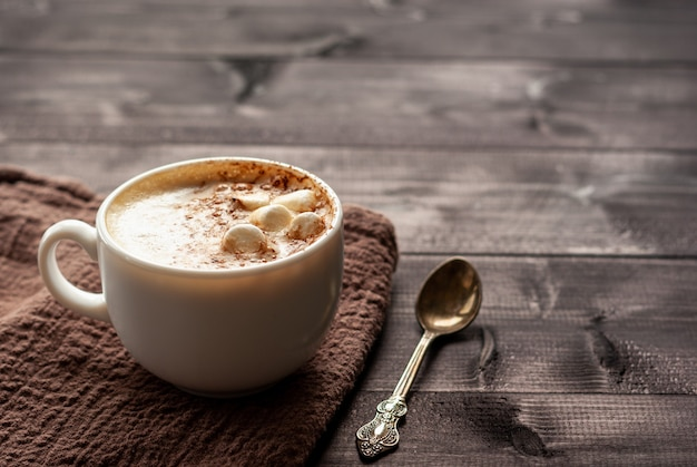 White cup of cappuccino with marshmallows and spoon on a wooden table. selective focus, copy space