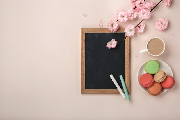 White cup cappuccino with sakura flowers, macarons, chalk board on a pastel pink background