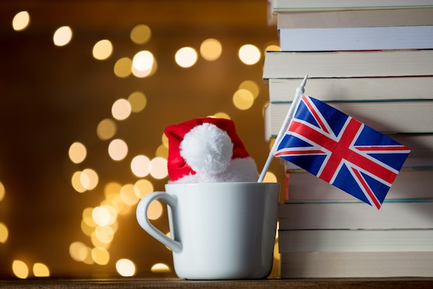 White cup and christmas hat with great britain flag near books