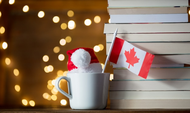 White cup and christmas hat with poland flag near books