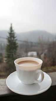 White cup of coffee on abstract nature background. one coffee mug on the balcony with a view of the nature behind. ceramic cup with a drink on the hotel balcony.
