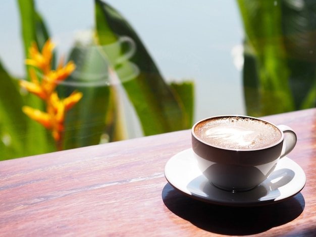 White cup of coffee cappuccino on wooden table beside glass window